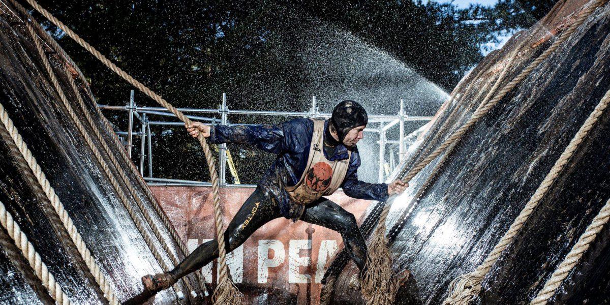 Athlet überwindet in der Nacht ein Wasserhindernis