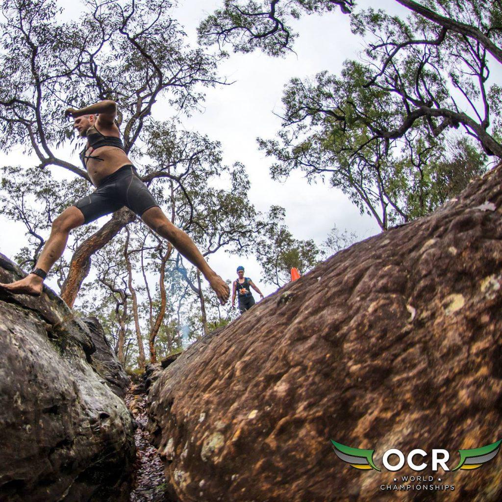 Athlet springt über Felsspalt
