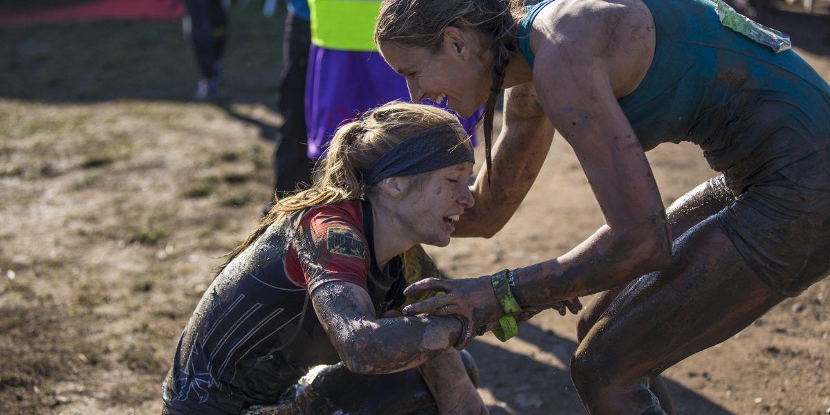 Sportlerin unterstützt Athletin im Ziel